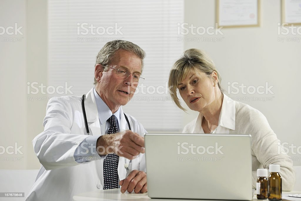 senior male doctor treating female patient royalty-free stock photo