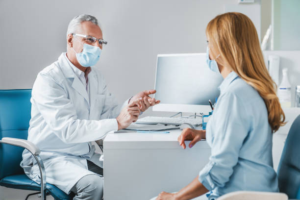Senior male doctor wear protection face mask talking with patient in clinic office Senior male doctor wear protection face mask talking with patient in clinic office doctors office stock pictures, royalty-free photos & images