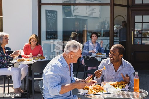 Cheerful male friends eating lunch together on sunny day, seaside, friendship, enjoyment