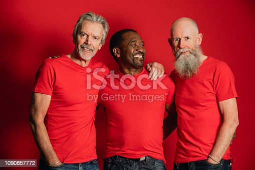 Portrait of three senior men standing in front of a red background. They are all wearing matching red t-shirts.