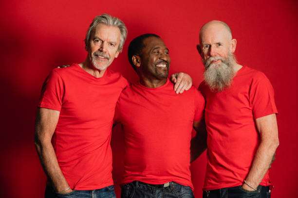 Senior Male Friends Laughing Portrait of three senior men standing in front of a red background. They are all wearing matching red t-shirts. red shirt stock pictures, royalty-free photos & images