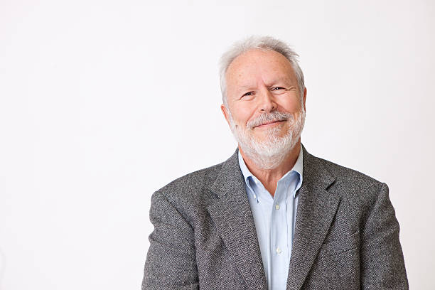 Senior male in gray jacket posing against white background stock photo