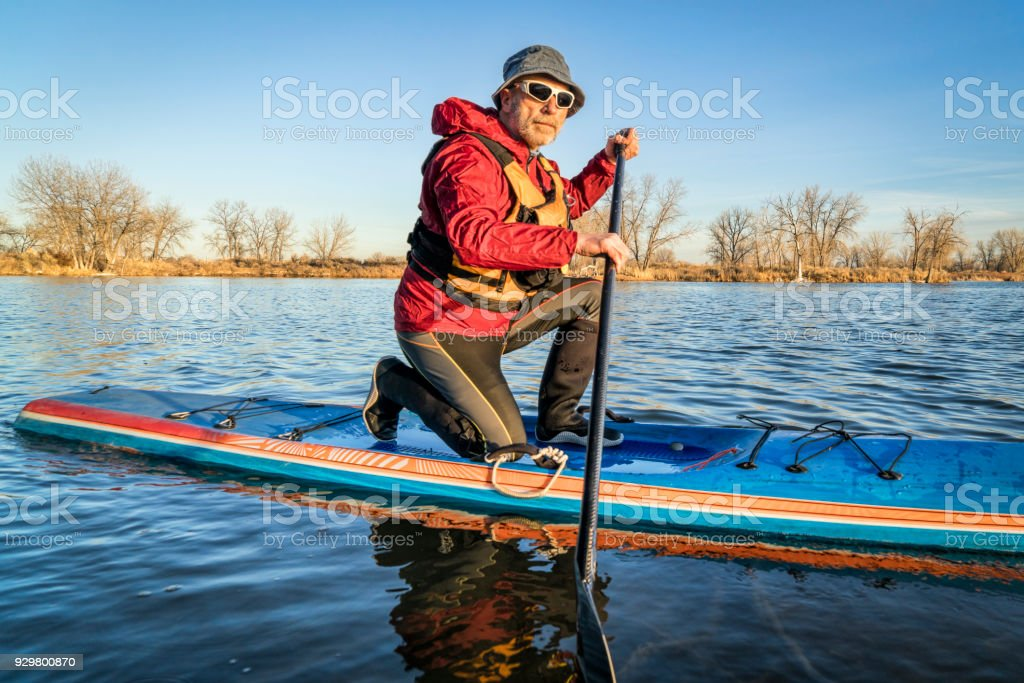 senior male paddler on a racing stand up paddle board, a lake in...