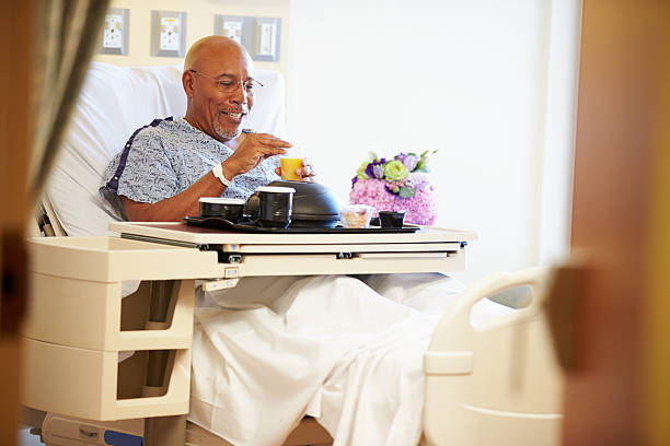 Senior Male Patient Enjoying Meal In Hospital Bed Senior Male Patient Enjoying Meal On Tray In Hospital Bed patience stock pictures, royalty-free photos & images