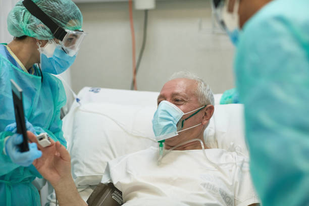Senior Male Patient Enjoying Video Call from Hospital Bed stock photo