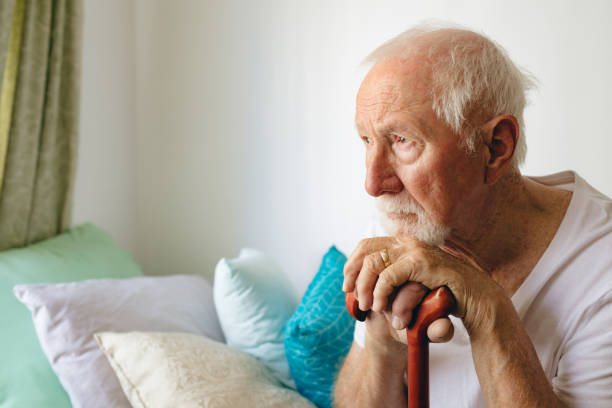 Senior male patient sitting upset on bed with stick at retirement home stock photo
