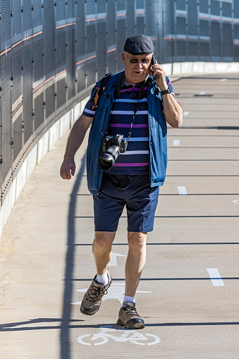 Senior male photographer walking on protected walkway talking on mobile phone, with DSLR camera