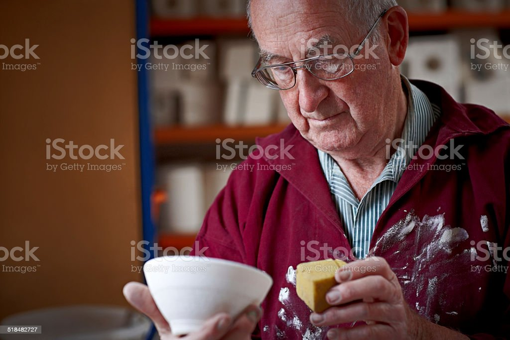 Senior male potter giving finishing touch to a clay pot stock photo