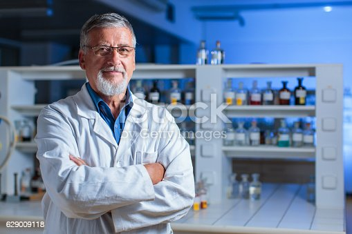 Senior male researcher carrying out scientific research in a modern lab, preparing chemical compounds, using microscope, scales and other high-tech laboratory equipment (shallow DOF; color toned image)