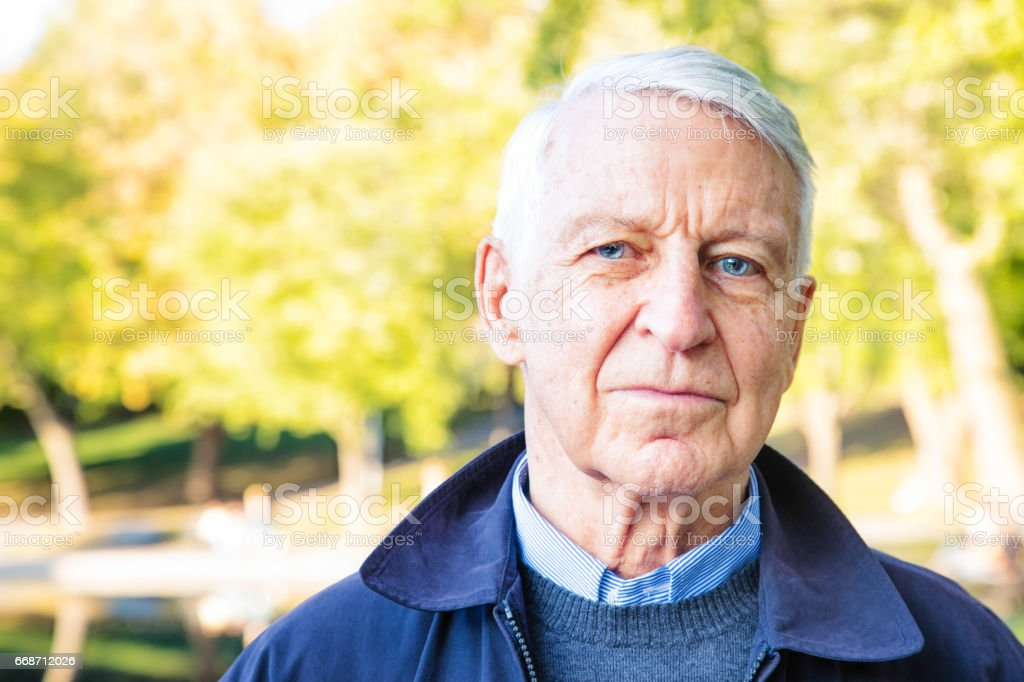 Senior male serious portrait in park on Autumn day stock photo