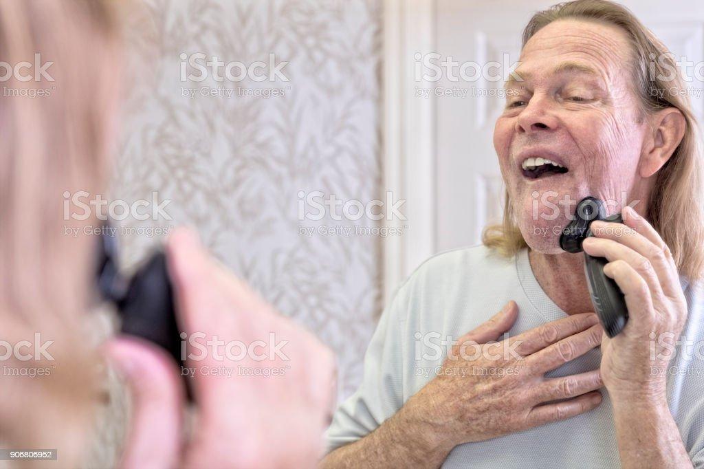 Senior male shaves off his beard stock photo