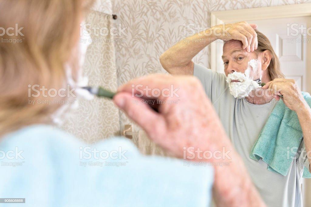 Senior male shaving off his beard stock photo