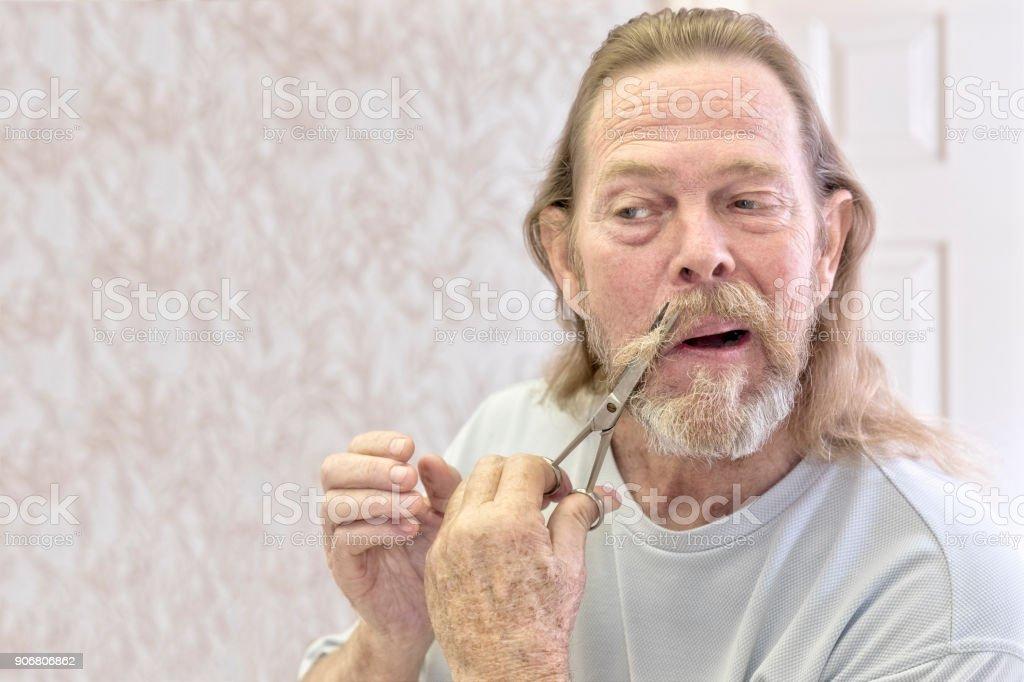 Senior male starts cutting his beard off with scissors stock photo