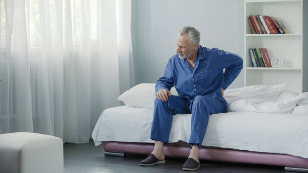 Senior male suffering sharp back pain, getting up from bed, morning stock photo