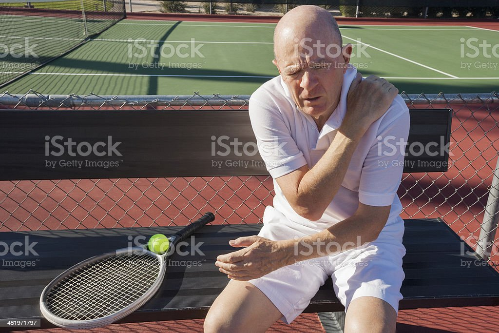 Senior male tennis player shoulder pain sitting at court stock photo