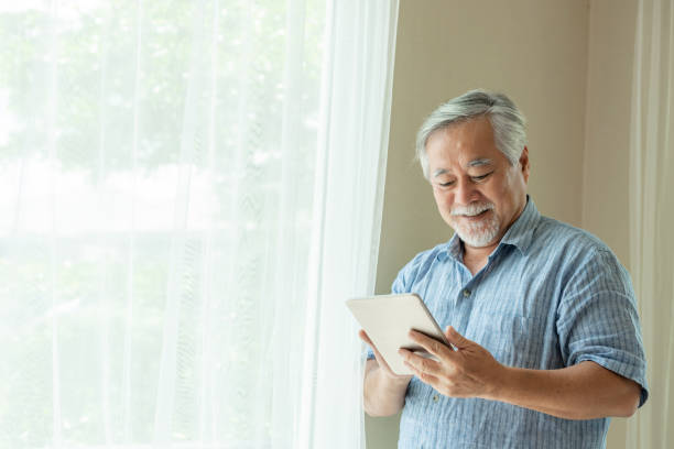 Senior Male using a smartphone , smiling feel happy in bedroom at home - lifestyle senior concept stock photo