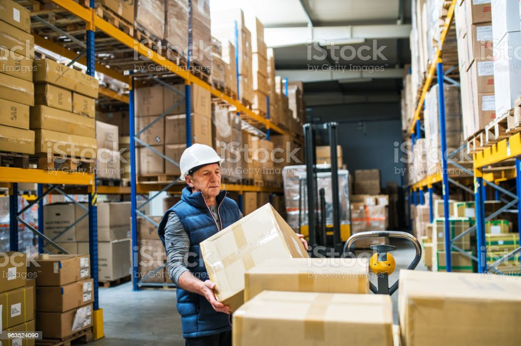 Senior male warehouse worker unloading boxes from a pallet truck. stock photo