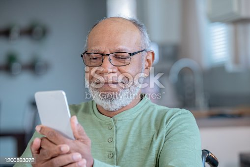 Senior male wearing eyeglasses uses mobile phone in domestic kitchen