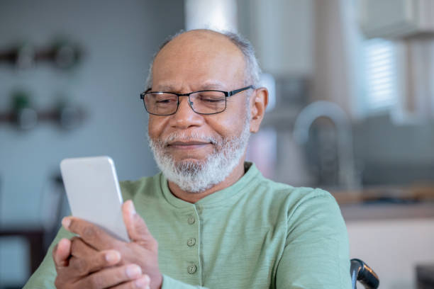 Senior male wearing eyeglasses uses mobile phone in domestic kitchen stock photo