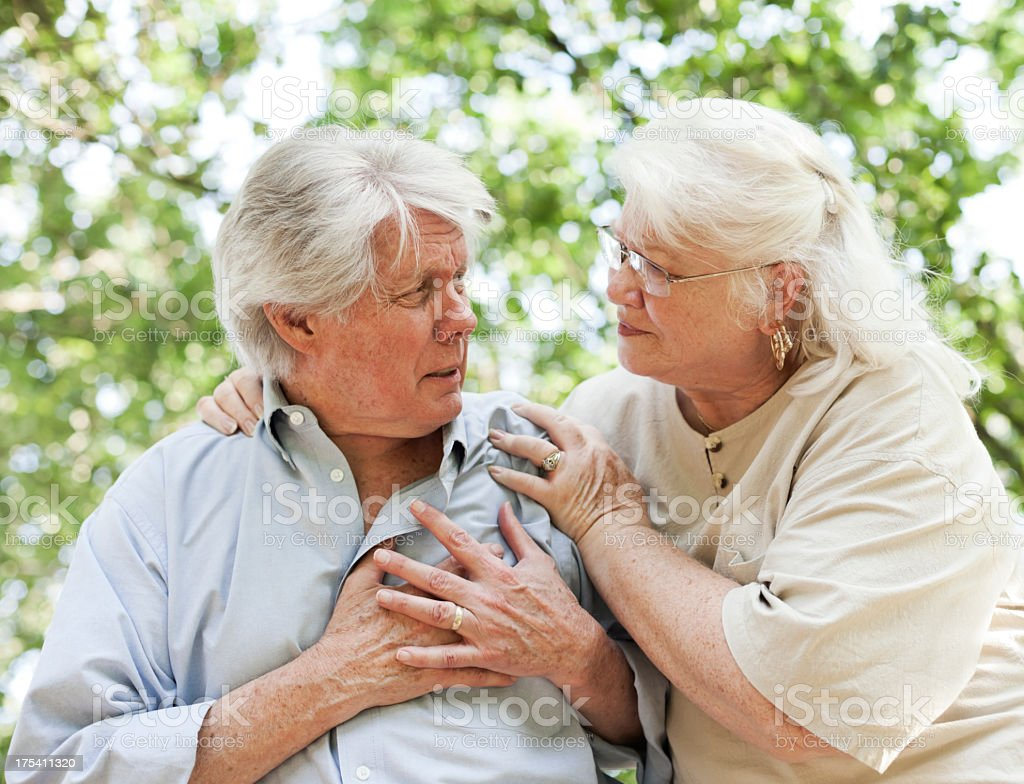 Senior male with hand on his chest embraced by his wife stock photo