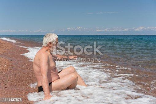 istock Senior man, a tourist enjoying the waves of Lake Issy-kul in Kyrgyzstan 1141437573