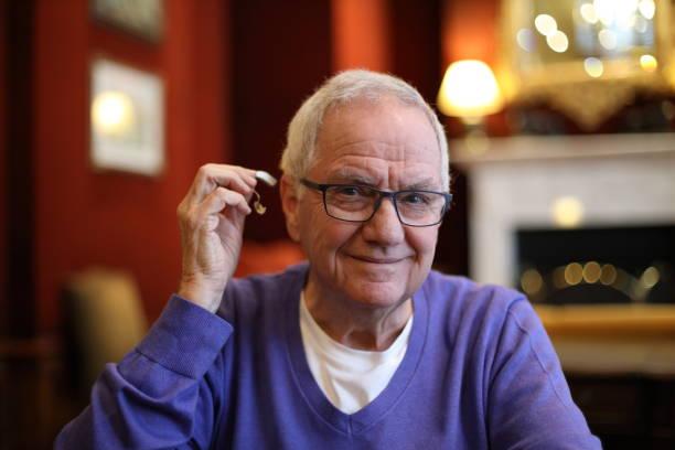 senior man over te voegen zijn gehoorapparaat - gehoorverlies stockfoto's en -beelden