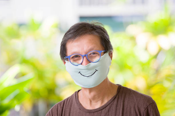 COVID-19 Senior Man Adjusting Homemade Face Mask for Social Distancing stock photo