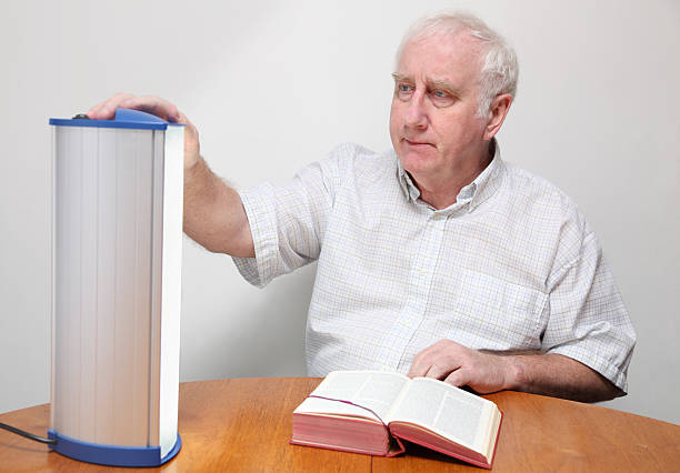 senior man adjusts seasonal affective disorder SAD lamp senior man adjusts seasonal affective disorder SAD lamp - these lamps simulate strong daylight and are believed to be effective i controlling  depression associated with lack of daylight in winter months -