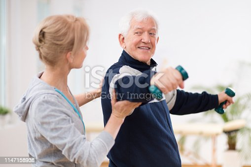 950649706istockphoto Senior man after stroke at nursing home exercising with professional physiotherapist 1147158938