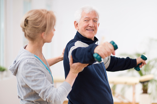 950649706 istock photo Senior man after stroke at nursing home exercising with professional physiotherapist 1147158938