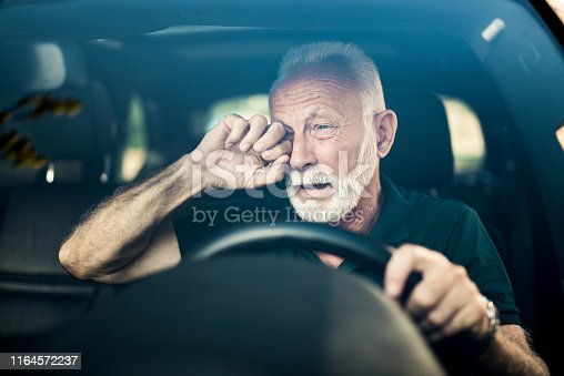 Senior man almost falls asleep while driving.