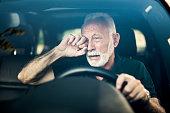 Senior man almost falls asleep while driving.