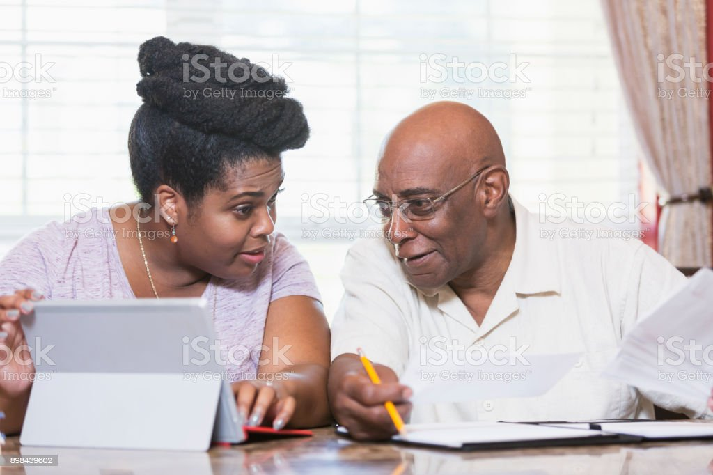 Senior man and adult daughter working on home finances stock photo