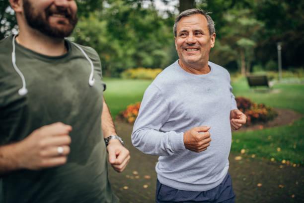 senior man en volwassen zoon joggen in park - mid volwassen stockfoto's en -beelden