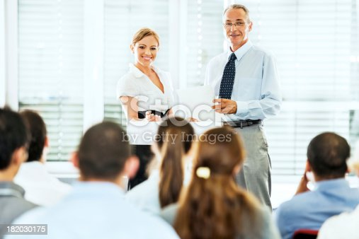 1180973515 istock photo Senior man and  blonde woman giving a public speech 182030175