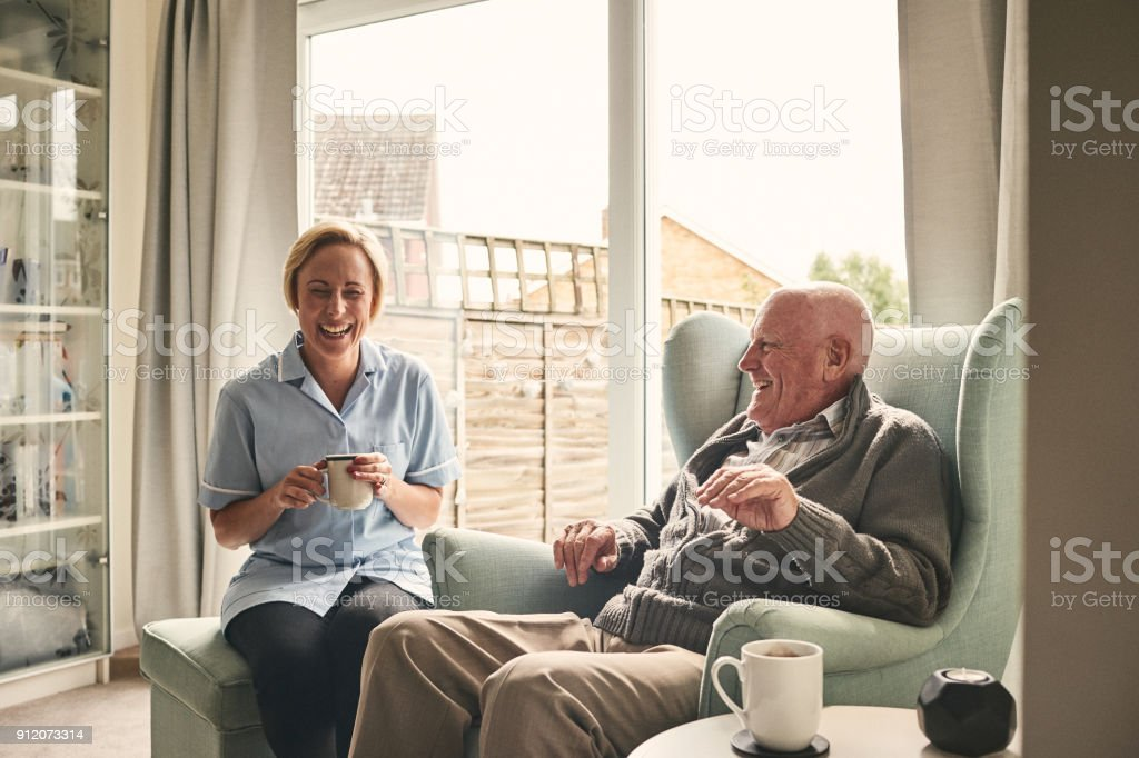 Senior man and female carer enjoying coffee at home stock photo