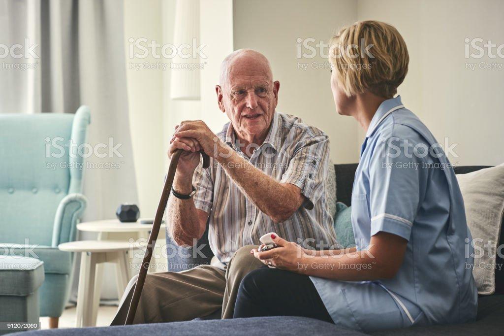 Senior Woman und weibliche Betreuer sprechen im Wohnzimmer – Foto