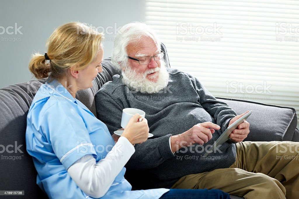 Senior man and female carer using digital tablet at home stock photo