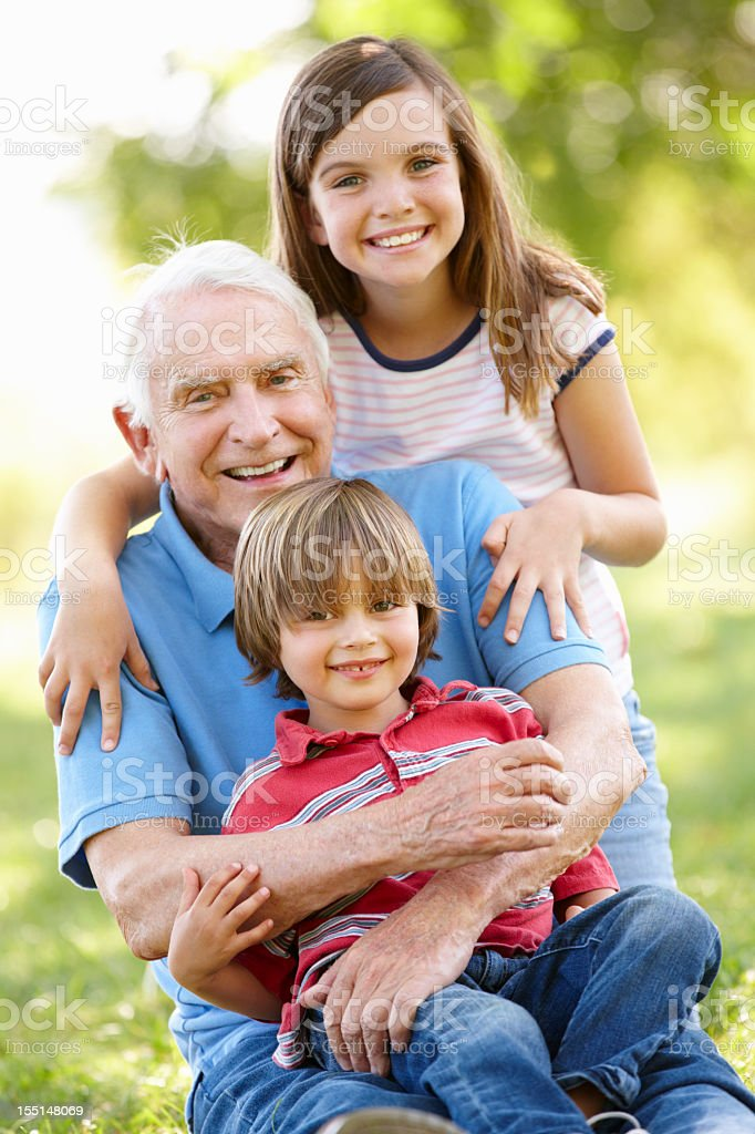 Senior man and grandchildren in park royalty-free stock photo