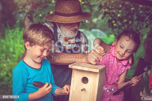 Grandfather and children making birdhouse outdoors in summer