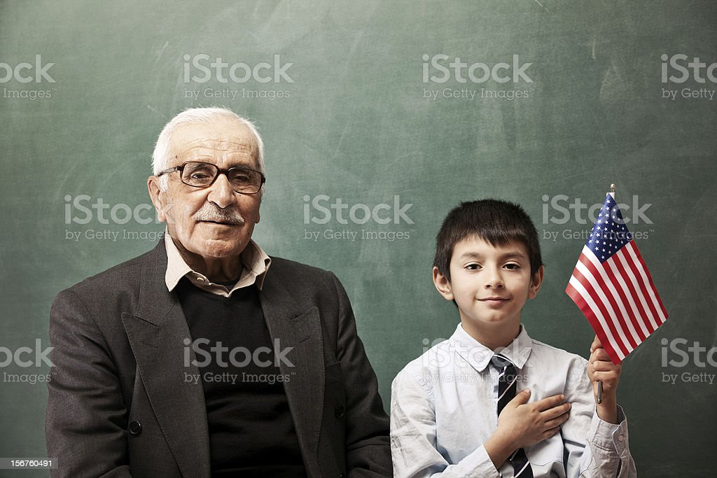 Senior man and little boy posing with American Flag royalty-free stock photo