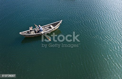 Aerial view of a man rowing a dory on the sea with a woman aboard.