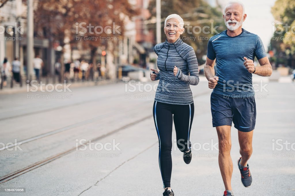 Senior man and senior woman jogging side by side on the street Couple of seniors jogging outdoors in the city Exercising Stock Photo