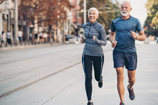 Couple of seniors jogging outdoors in the city
