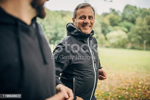Two men, senior man and his adult son jogging together in park.