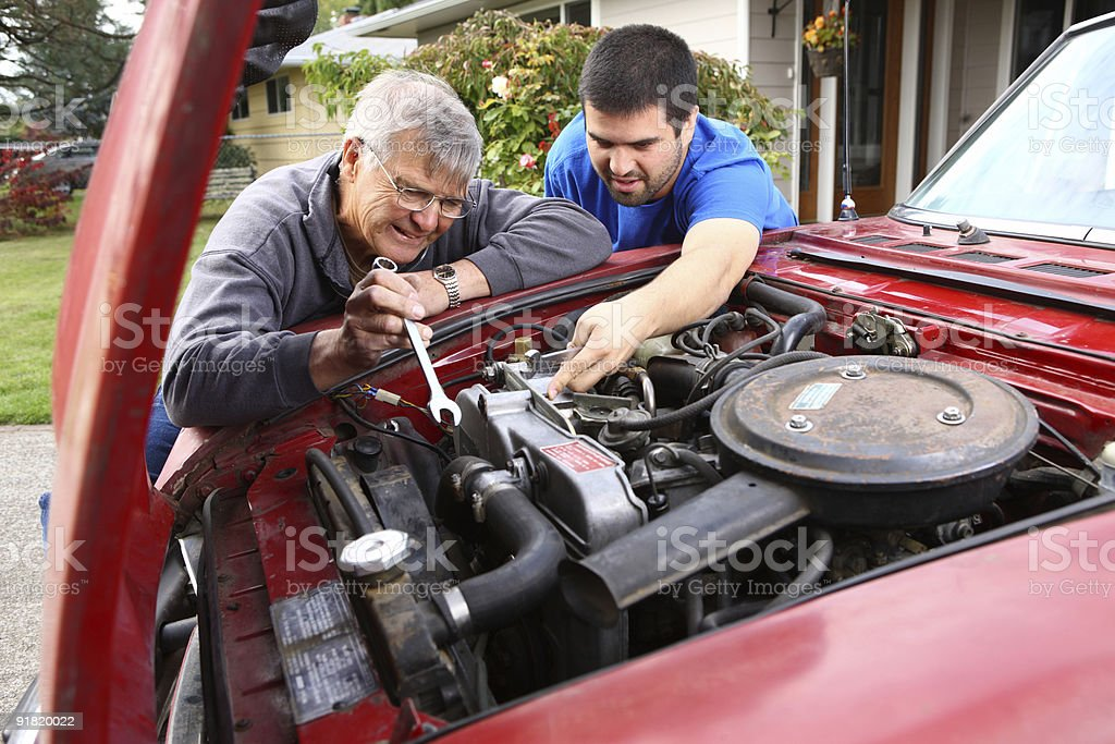 Senior man and son working on car engine stock photo