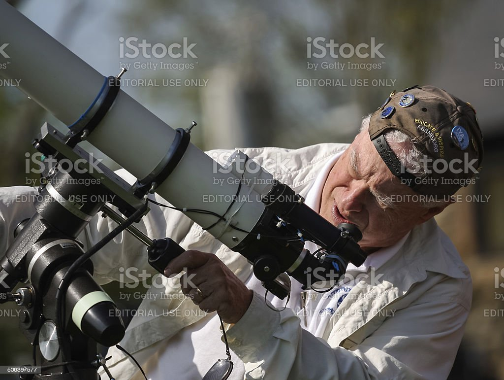 Senior man and volunteer amateur astronomer setting up a telescope stock photo