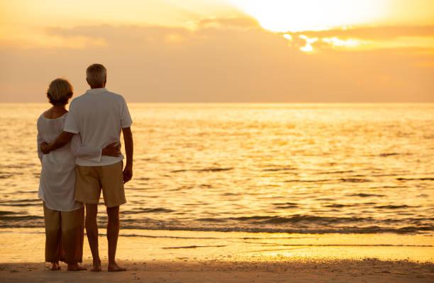 Pareja de hombres y mujeres mayores abrazando al atardecer o al amanecer en una playa tropical desierta - foto de stock