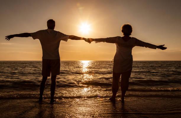 Pareja de hombres y mujeres de la tercera edad sosteniendo los brazos de par al atardecer o al amanecer en la playa tropical desierta - foto de stock