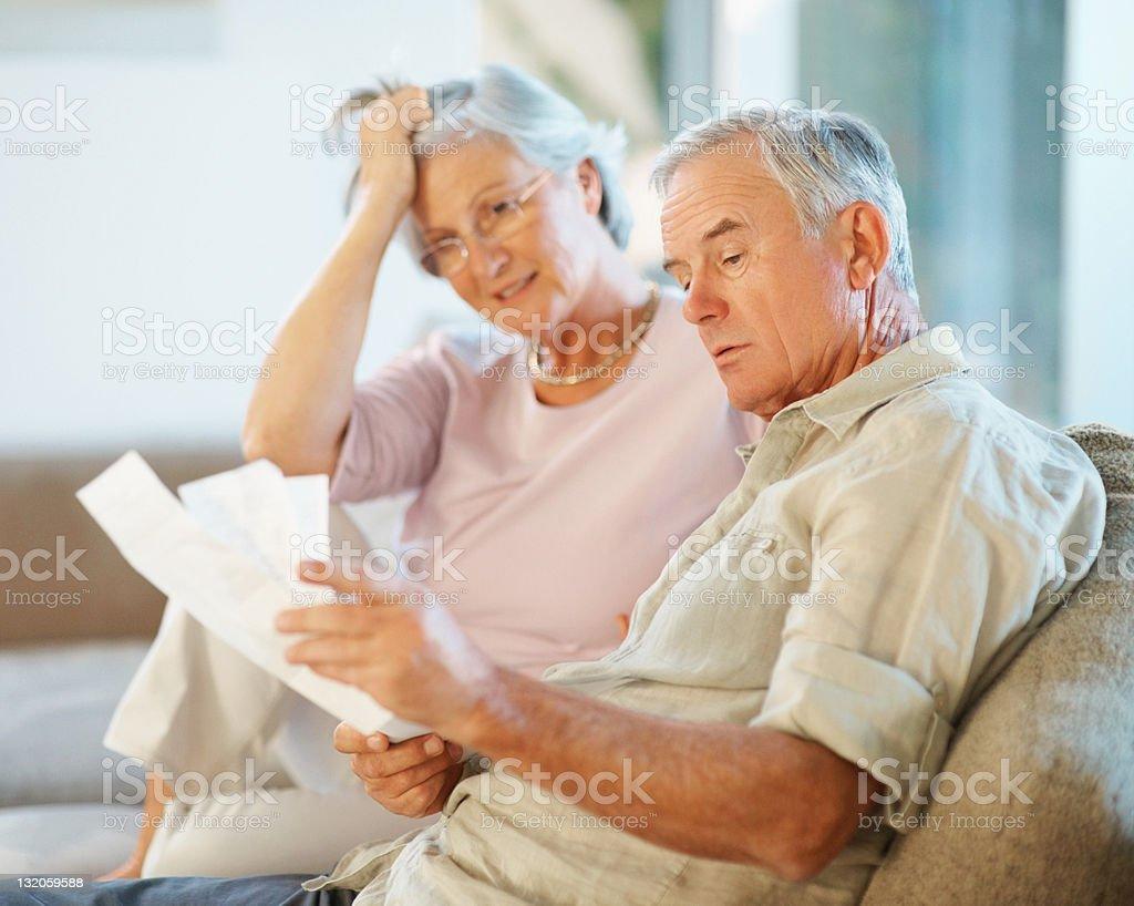 Alter Mann und Frau gehen durch die Zahlung Rechnungen – Foto
